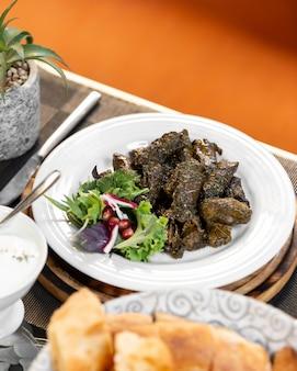 Hojas de uva azerbaiyana dolma servidas con ensalada de cebolla y hierbas de granada