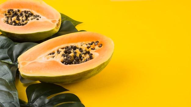 Hojas verdes artificiales con fruta de papaya a la mitad sobre fondo amarillo