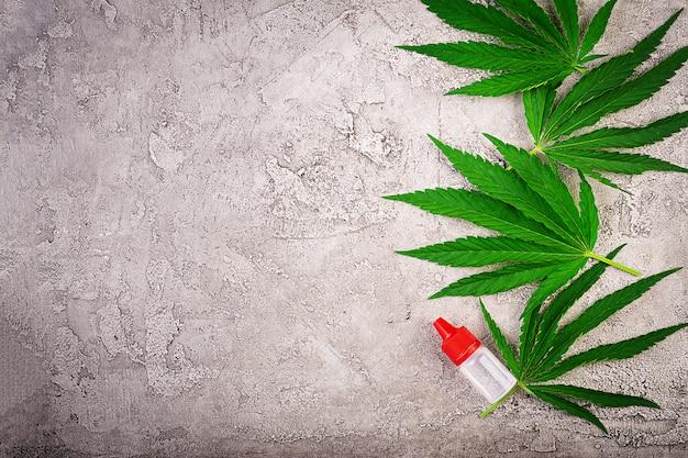 Hojas verdes de cannabis con aceite de cáñamo. vista superior.