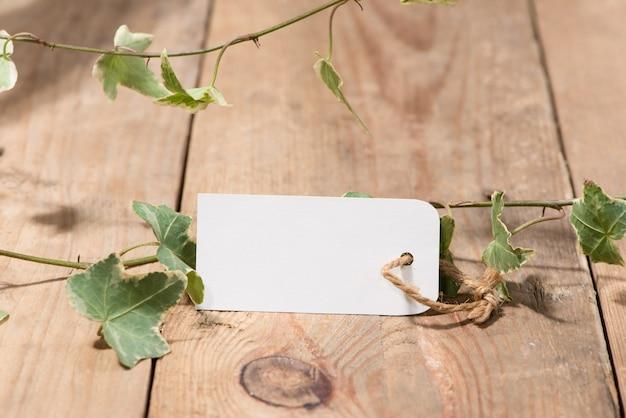 Hojas verdes con etiqueta en blanco sobre fondo de madera