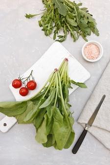 Hojas verdes frescas de la espinaca, arugula y tomates de cereza en un tablero de madera blanco con la sal rosada.