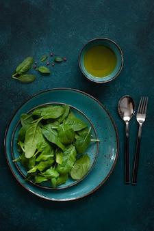 Las hojas verdes frescas de la espinaca del bebé con aceite de oliva en fondo verde