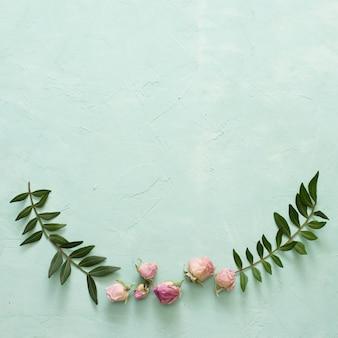 Hojas verdes y hermoso capullo de rosa sobre fondo verde con textura