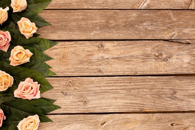 Hojas verdes y rosas sobre fondo de madera con espacio de copia.