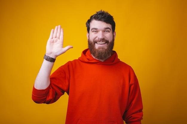 Hola amigos, hombre sonriente con barba en blusa roja haciendo gesto de hola