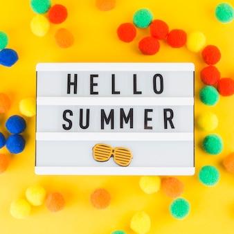 Hola, caja de luz de verano con coloridas bolas pequeñas de pom pom sobre fondo amarillo