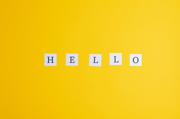 Hola cartel deletreado en papeles blancos post-it colocados sobre fondo amarillo.