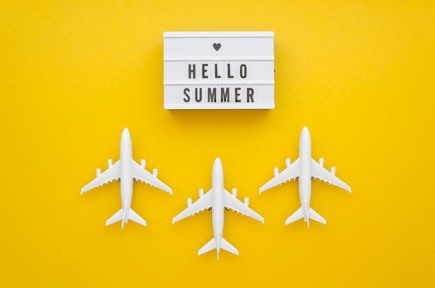 Hola etiqueta de verano con aviones en la mesa