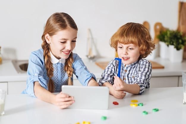 Hola. hermosos niños lindos optimistas haciendo una videollamada usando su dispositivo mientras su hermano explica lo que hacen durante el fin de semana