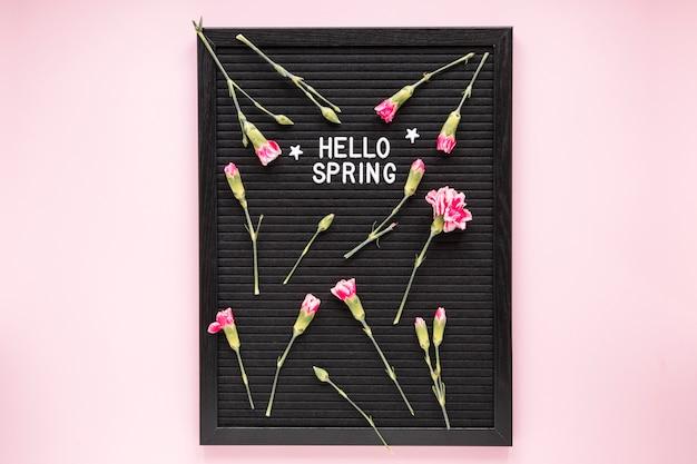 Hola inscripción de primavera con flores sobre tablero negro.