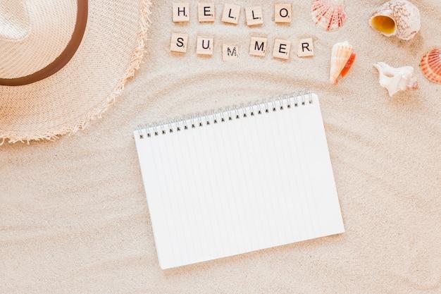 Hola inscripción de verano con sombrero de paja y cuaderno.