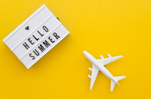 Hola mensaje de verano al lado del avión de juguete