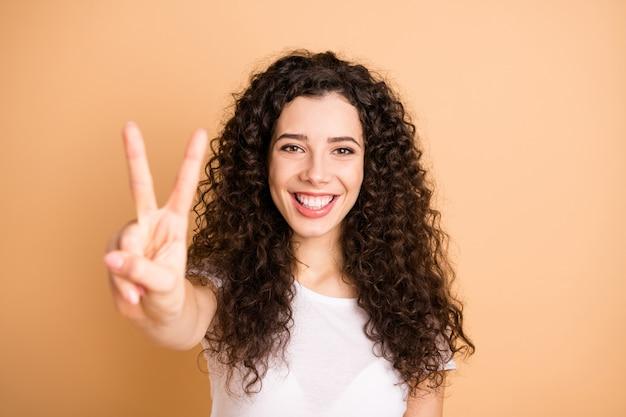 ¡hola mundo maravilloso! foto en primer plano de una dama increíble que muestra el símbolo v-sign, estado de ánimo positivo, ropa casual blanca, aislado de fondo de color beige pastel