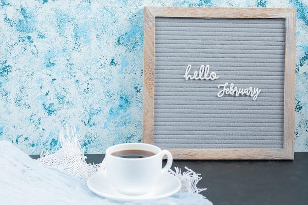 Hola nombres de meses en el tablero con una taza de bebida alrededor