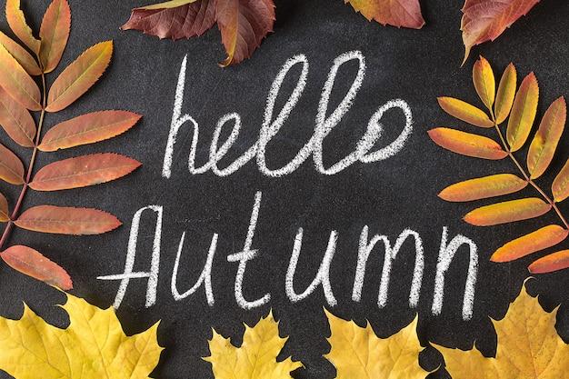 Hola otoño tiza blanca letras en la pizarra.