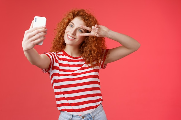 Hola seguidores, cómo son tus vacaciones de verano. alegre, segura de sí misma, elegante, elegante, pelirroja, rizada, niña, huelga, pose, mostrar, paz, victoria, gesto, mirar, smartphone, pantalla, toma, autofoto, fondo rojo.
