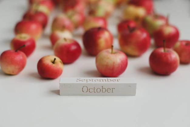 Hola tarjeta de otoño de octubre con manzanas rojas frescas en la vista superior de fondo blanco
