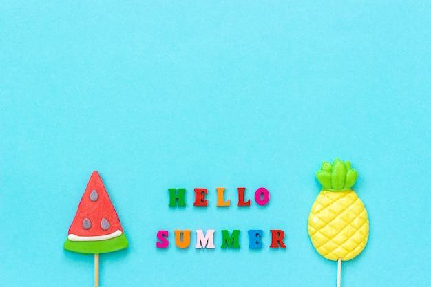 Hola texto colorido de verano, piruletas de piña y sandía en palo sobre fondo de papel azul.