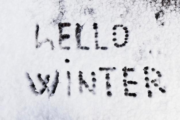 Hola texto de invierno escrito en la nieve.