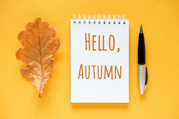 Hola texto de otoño en el bloc de notas, hoja de roble naranja seca y pluma sobre fondo amarillo. vista superior endecha plana tarjeta de felicitación