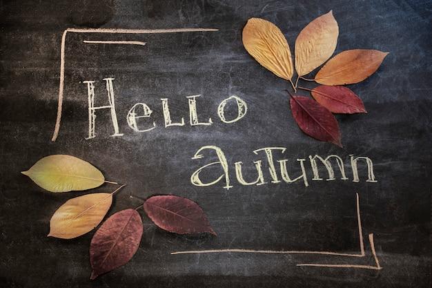 Hola texto de saludo de otoño en la pizarra. fondo de junta escolar de madera oscura con hojas de arce de colores.