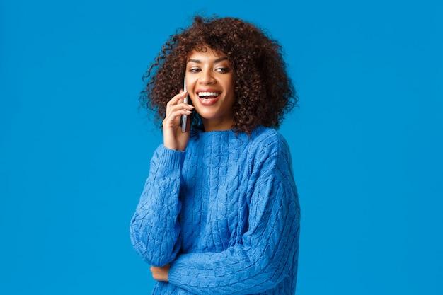 Hola ven linda amigable y carismática mujer afroamericana invitando a amigos a la fiesta de fin de año, celebrar las vacaciones juntos, llamar a su compañero por teléfono, sostener el teléfono inteligente y reír