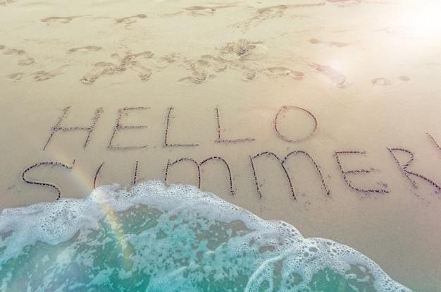 Hola verano escrito en la playa