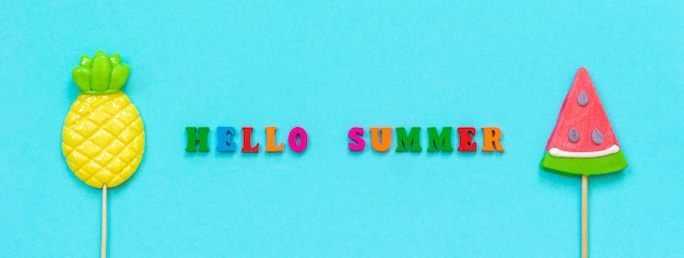 Hola verano texto colorido, piña y sandía paletas concepto vacaciones o días festivos banner