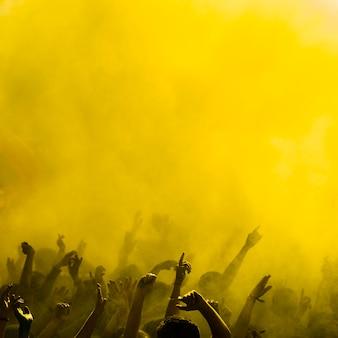 Holi color amarillo sobre las personas bailando.