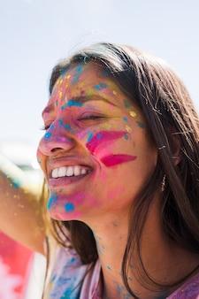 Holi de color sobre el rostro de la mujer sonriente.