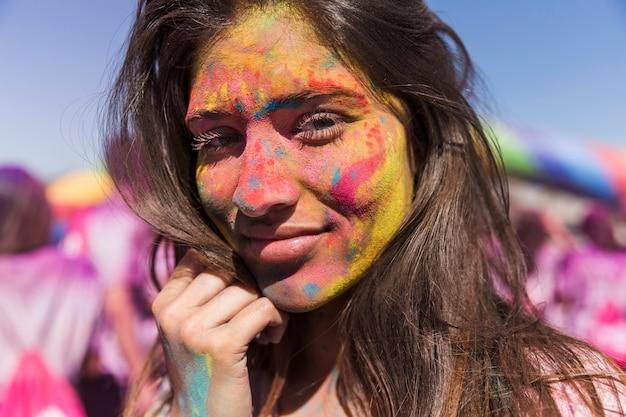 Holi colorido en la cara de la mujer.