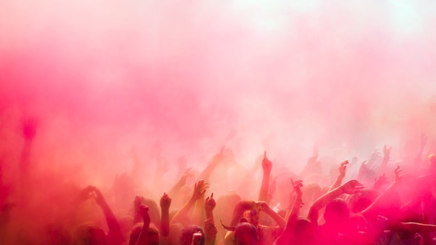 Holi rojo y rosa sobre la multitud.