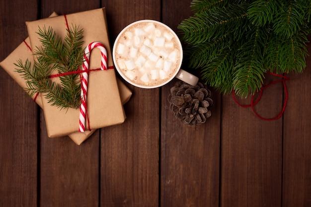 Holiday flatlay, regalos envueltos con papel artesanal, con bastón de caramelo y taza de café en una mesa rústica de madera oscura.