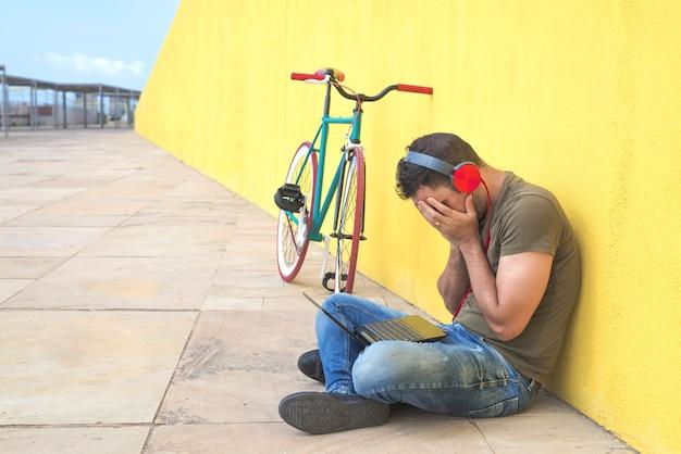 Hombre abandonado perdido en la depresión sentado en la calle del suelo sufriendo dolor emocional, tristeza y mirando destruido y desesperado apoyándose solo en la pared