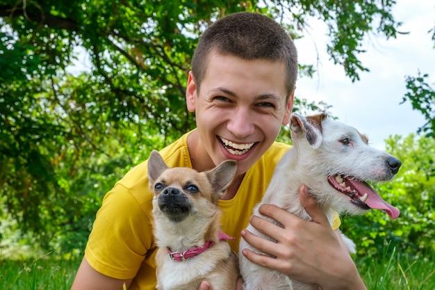 El hombre abraza a dos perros jack russell y un chihuahua y se ríe alegremente en el parque