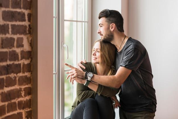 Hombre abrazando a su novia señalando algo cerca de la ventana