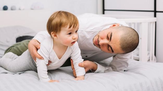 Hombre abrazando al pequeño bebé acostado en la cama