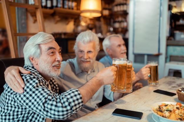 Hombre abrazando a un amigo. hombre jubilado abrazando a un amigo mientras ve el fútbol juntos en el pub