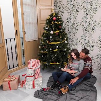 Hombre abrazando a una mujer desde atrás con un regalo en una colcha cerca del árbol de navidad