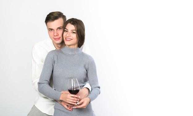 Hombre abrazando a mujer con copa de vino