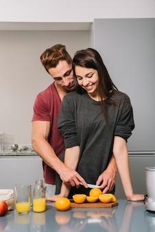Hombre abrazando a la mujer por detrás y cortando naranja