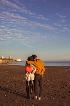 Hombre abrazando a mujer con globo de corazón en la orilla del mar