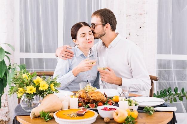 Hombre abrazando a la mujer en la mesa festiva