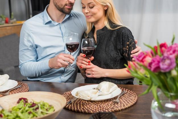 Hombre abrazando a la mujer en la mesa con flores y plato de ensalada