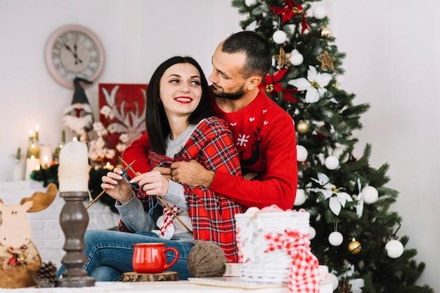Hombre abrazando a mujer tejiendo cerca de árbol de navidad
