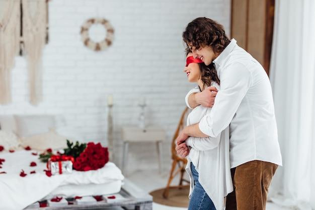 El hombre abrazando a la novia con los ojos vendados en los ojos haciendo sorpresa para el día de san valentín