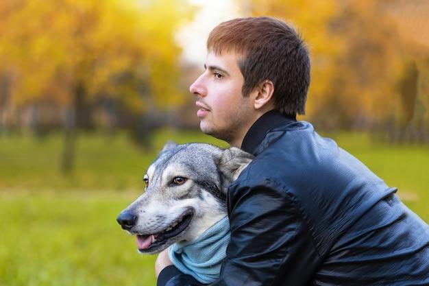 Hombre abrazando a perro. adopción de mascotas. checoslovaco con dueño masculino. niño caminando, jugando, entrenando saarlos wolfdog