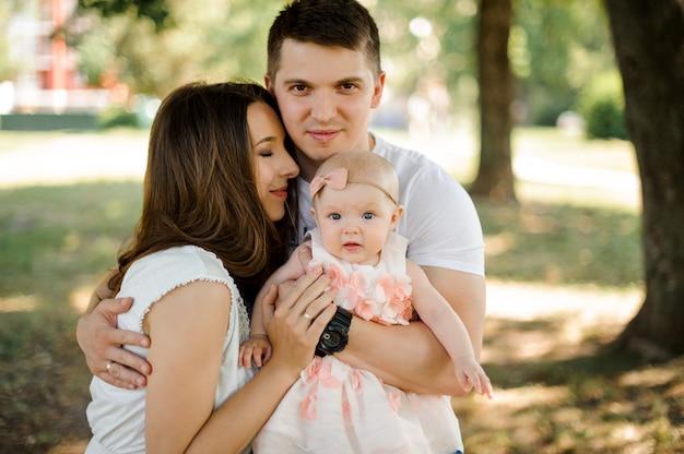 Hombre abrazando a su encantadora esposa y linda hijita