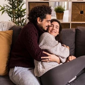 Hombre abrazando a su esposa por detrás