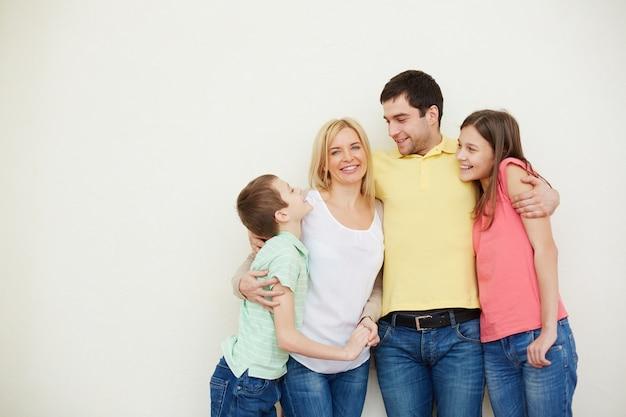 Hombre abrazando a su familia idílica